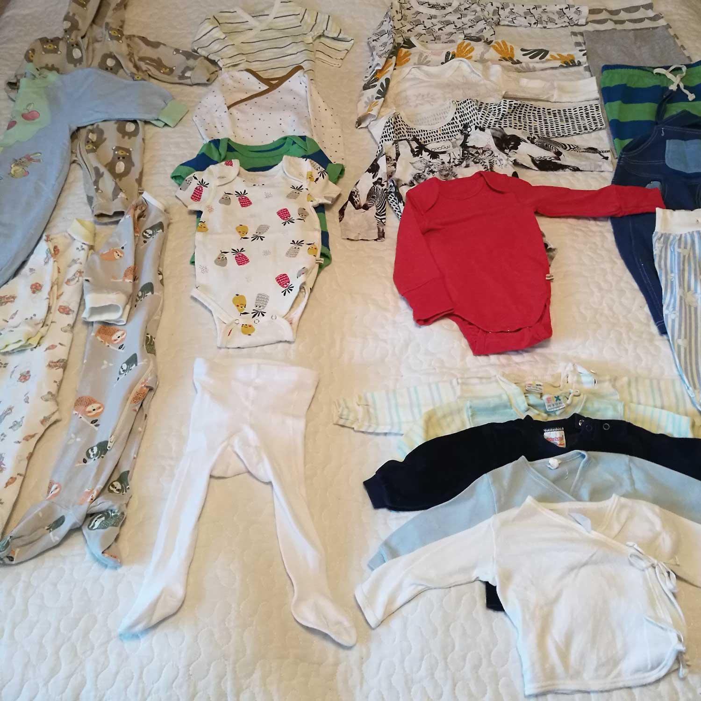 Sängylle on levitetty näytille neljä erilaista haalaria, sukkahousut, viisi paitaa, viidet housut ja kymmenen bodya.