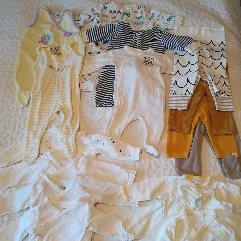 Sängylle on levitetty näytille parit kellertävät potkuhousut, kolme haalaria, neljät housut, neljä vaaleaa kietaisubodya ja kolme paitaa.
